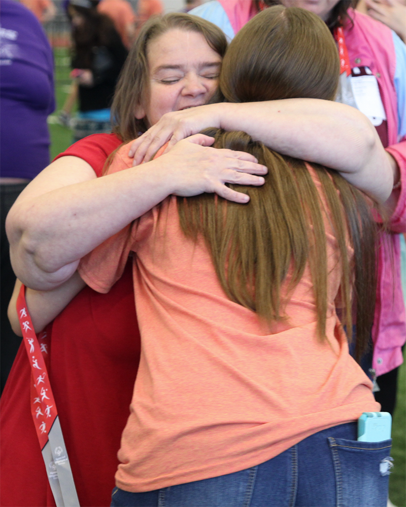 Junior+Morgan+Noe%2C+a+GBL+Club+Volunteer%2C+embraces+a+Special+Olympic+athlete+after+awarding+her+with+a+medal.