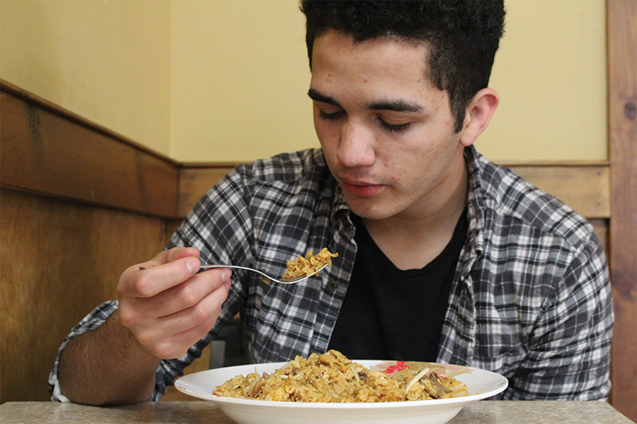 Senior Andres Munguia eats rice and chicken at Happy Family.