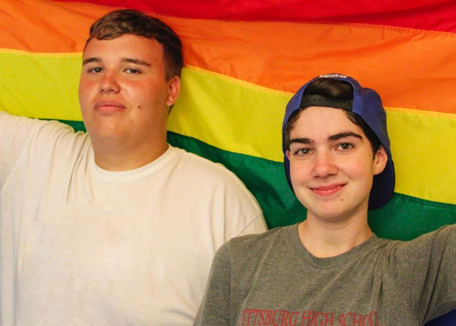 Senior Tayten Kelsey (left) and 2018 graduate Ky Barnhisel (right) drape up the LGBTQ+ Pride flag.