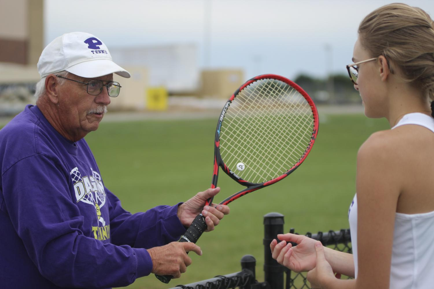 Head coach John Seal conferences with junior Sophia Shope after a match. Seal has coached Shope for her sophomore and junior years and also earned over 700 wins in his coaching career.