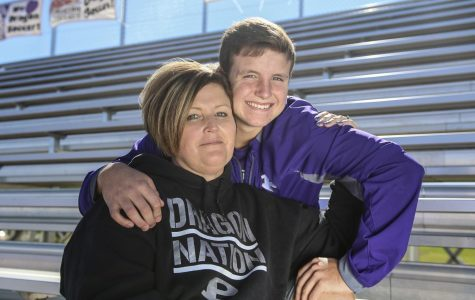 Sitting on the soccer bleachers, junior Caden Bressler embraces his mom, Trasie, who was diagnosed with breast cancer last spring. Caden plays varsity soccer and Trasie is a member of the soccer booster club.
