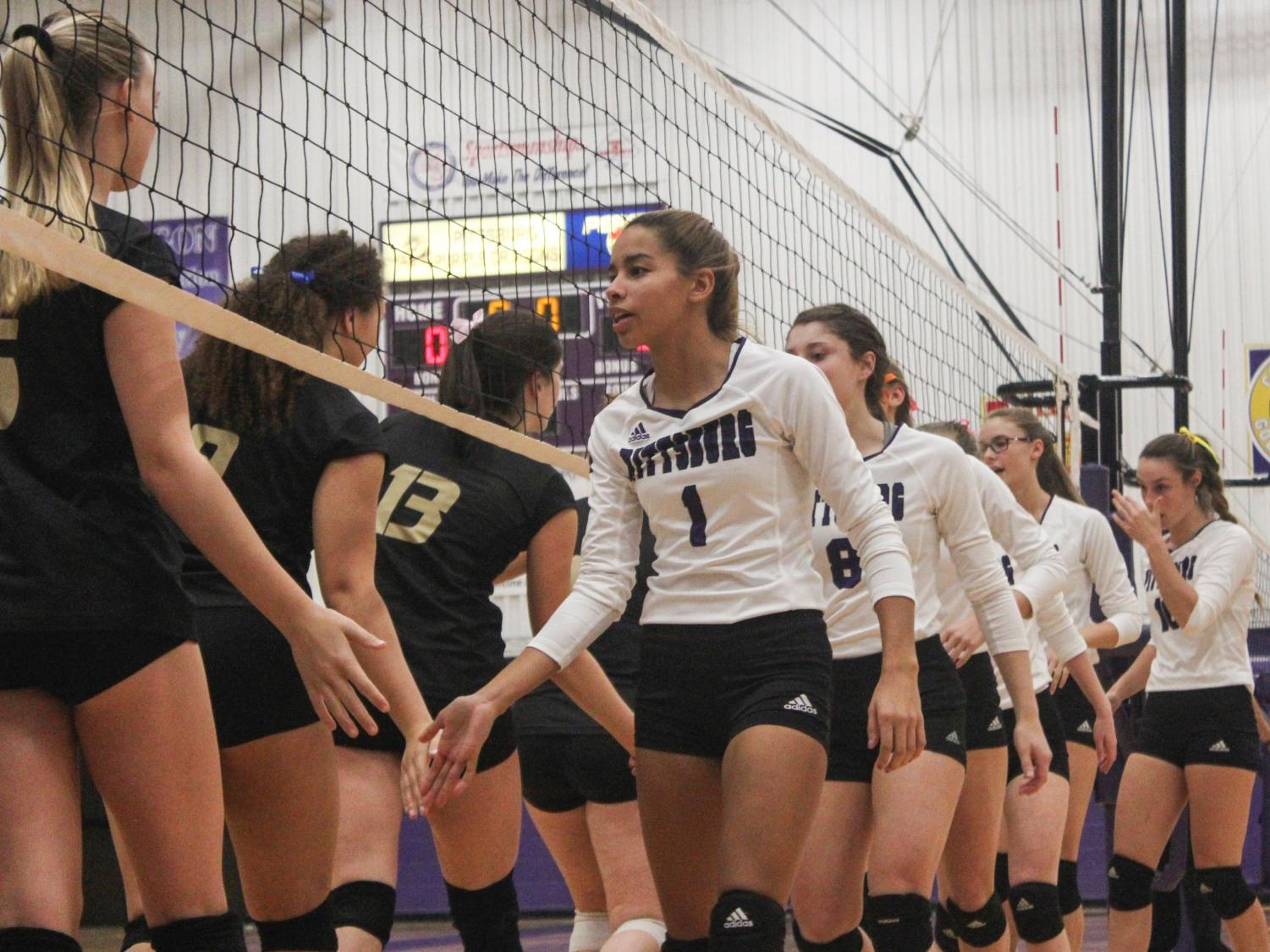 Preparing to start the game against Paola, junior Faith Turner and members of the varsity team slap hands before the first match, Phs defeated Paola in three matches, 25-11, 25-22,25-20.