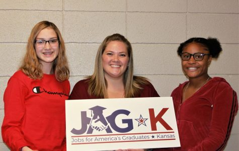 Adelina Tice, JAG teacher Jessica Thomas and I'sis Thomas stand with the new JAG sign.