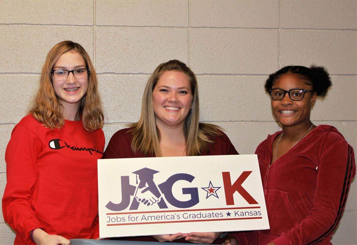 Adelina Tice, JAG teacher Jessica Thomas and I'sis Thomas stand with the new JAG sign. PHOTO BY LANE PHIFER