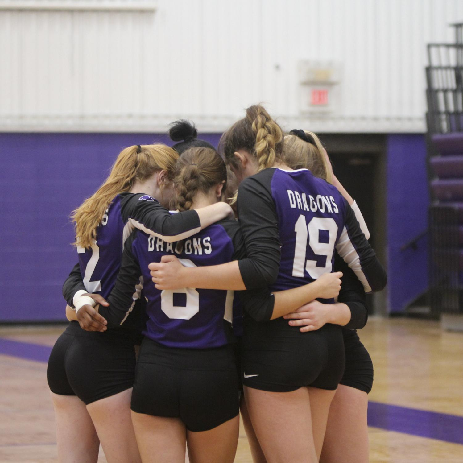 Members of the jv volleyball team huddle during a home tournament. The team finished the season 55-0.