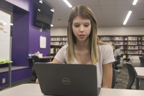 Sarah Stebbins works in the library while taking her online class.