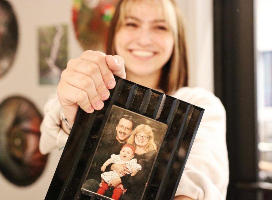 Senior Franchesca Brownhanney poses with a family photo from when she was first adopted.