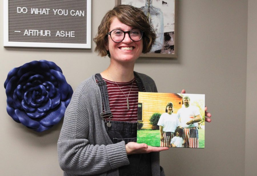 School counselor Stef Loveland poses along side a photo of her and her adoptive parents.