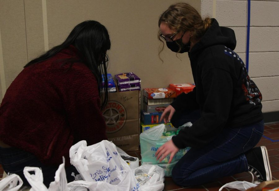 Senior Maddie Ellis (left) and freshmen Katie Davis (right) help stack food and hygiene products that were donated to a food drive hosted by the Culinary Dragons and Student Council.