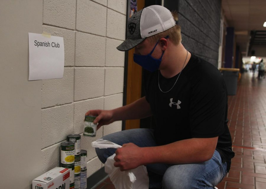 Senior Daniel Parker stacks food and hygiene products that were donated to the food drive that he created with the help of the Culinary Dragons and Student Council.