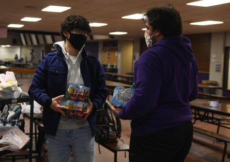 Seniors Joseph Lee (left) and Christopher Saman (right) discuss the donations National Honors Society made for a food drive hosted by the Culinary Dragons and Student Council.