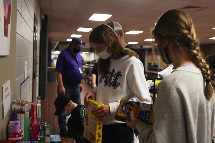 Junior Abby Painter stacks food that was donated to a food drive hosted by the Culinary Dragons and Student Council.