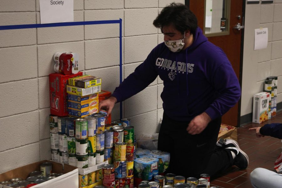 Senior Christopher Saman stacks food that was donated to a food drive put together by the Culinary Dragons and Student Council.