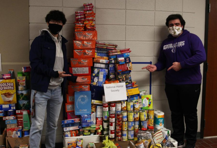 Seniors Jospeh Lee (left) and Christopher Saman (right) pose next to the donations National Honors Society made to a food drive the Culinary Dragons and Student Council put together.