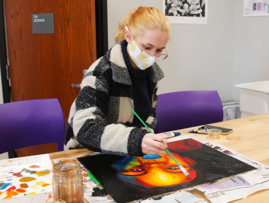 Senior Audrey Goode continues work on her portrait project in Rolanda Root's creative studio.