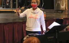 Choir director Susan Laushman conducts students in Encore while preparing contest submissions.