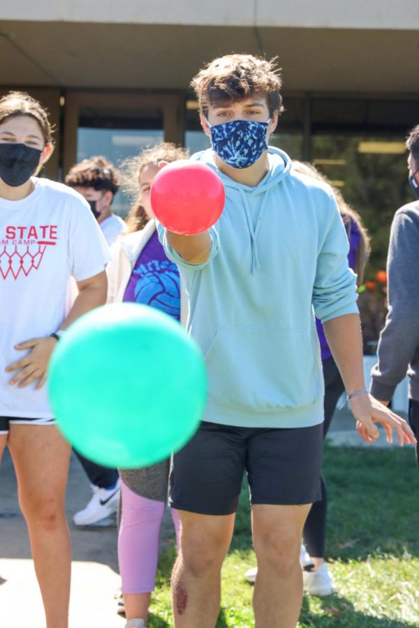 """Freshman Stone Peery throws the ball towards the bucket during the Spanish 1 ball activity. """"I was having lots of fun losing and messing with my friends playing the game, because I couldn't get the ball in the basket,"""" Peery said. """"It was a lot harder than it looked!"""""""